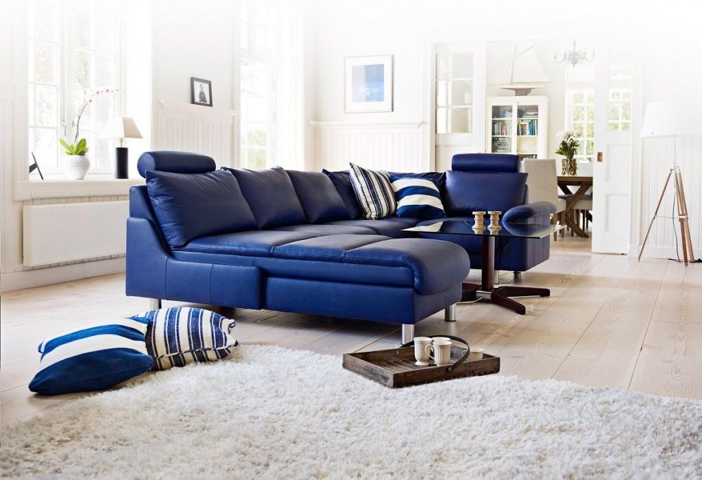 O canapea albastra si un covor alb sau argintiu